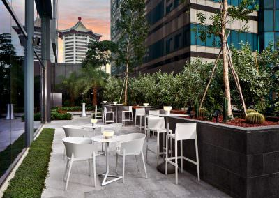 architectural photography of the terrace at yotel in singapore with seating and greenery at dusk