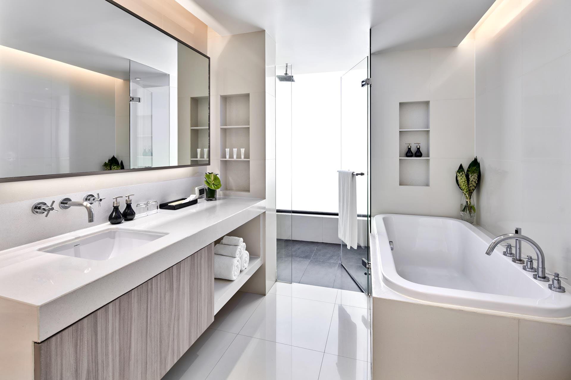 Luxury hotel bathroom photo with bathtub and shower with towel on door